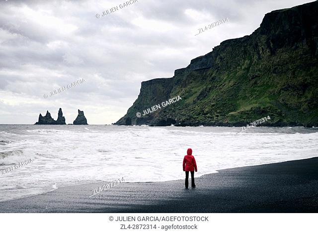 Iceland, Sudurland region, Vik i Myrdal, Vik beach, woman on the black sand beach and Reynisdrangur sea stacks, Model Released