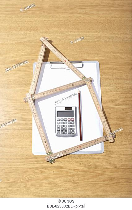 still life of folding rule in shape of house clipboard and calculator