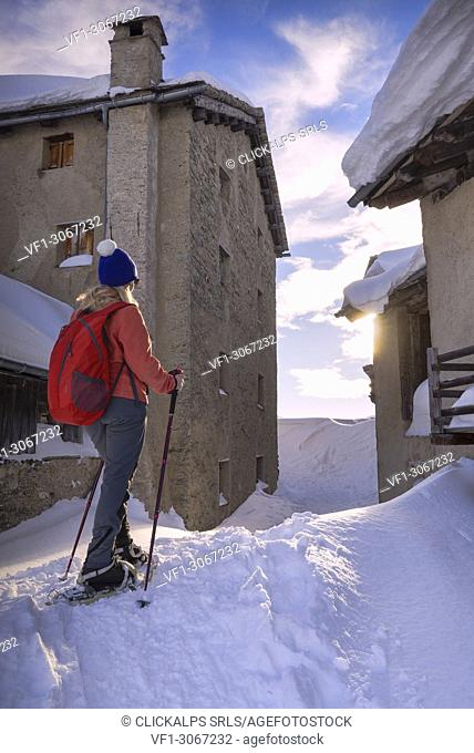 Young girl walk with snowshoes in the village of Grevasalvas at sunset. Engadin Valley, Graubünden, Switzerland, Europe