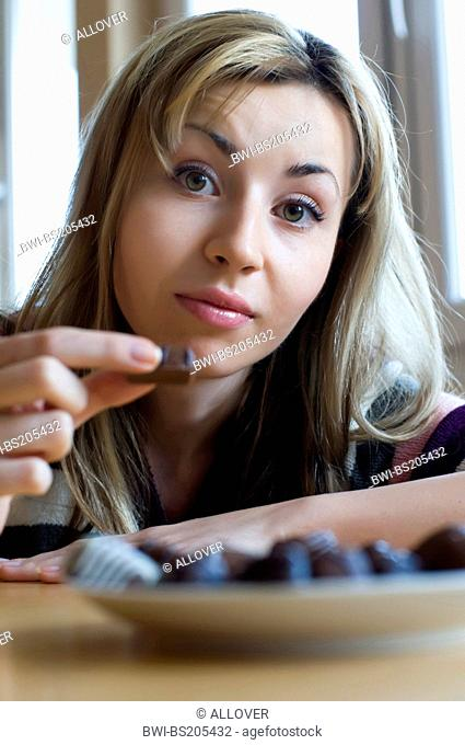 young woman with praline in hand