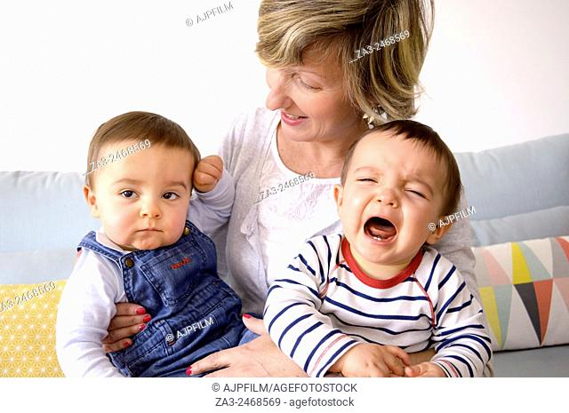 One year old twin brothers sitting on their mother's knee and one is crying
