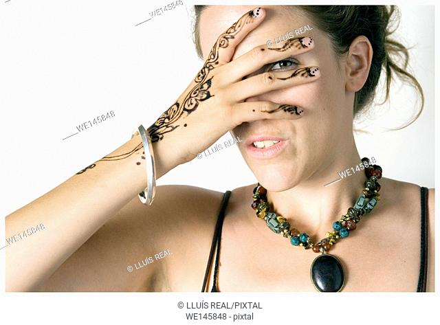 Closeup of young woman with henna tattoo on her hand covering her face and looking with one eye through the fingers