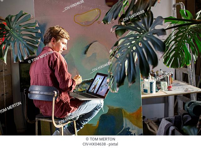 Male artist painting and using laptop in art studio