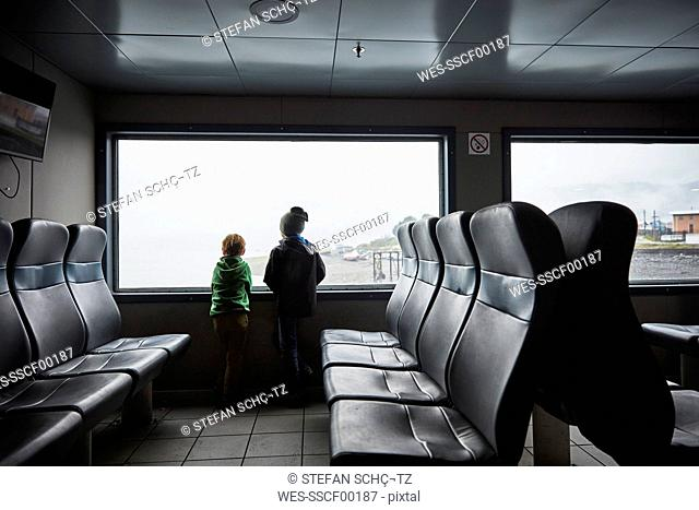 Chile, Puerto Montt, two boys looking out of window of a ferry