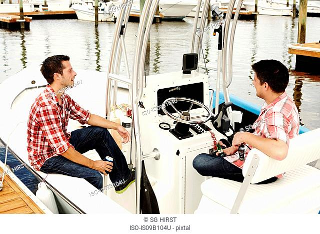 Two adult brothers relaxing on motorboat in marina