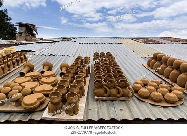 Unfired pottery or greenware dries on the tin roof of a pottery workshop in San Antonio Palopó, Guatemala