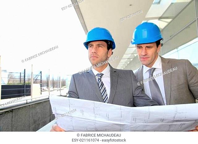 Architects checking construction site with plan outside