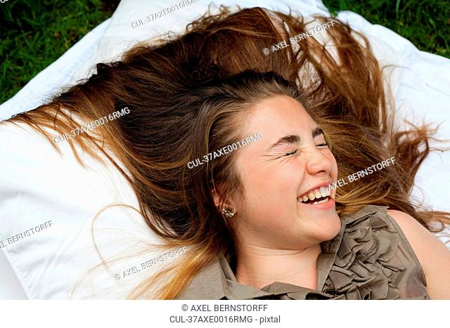 Teenage girl laughing on pillows