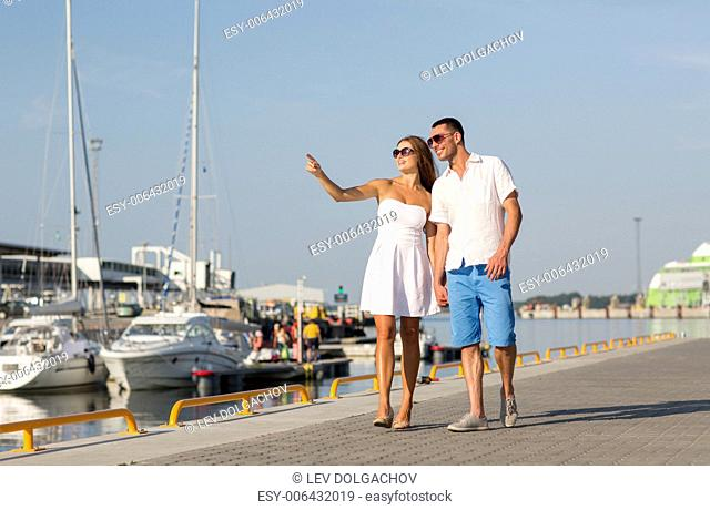 love, travel, tourism, sailing, people and friendship concept - smiling couple wearing sunglasses walking at harbor and pointing finger