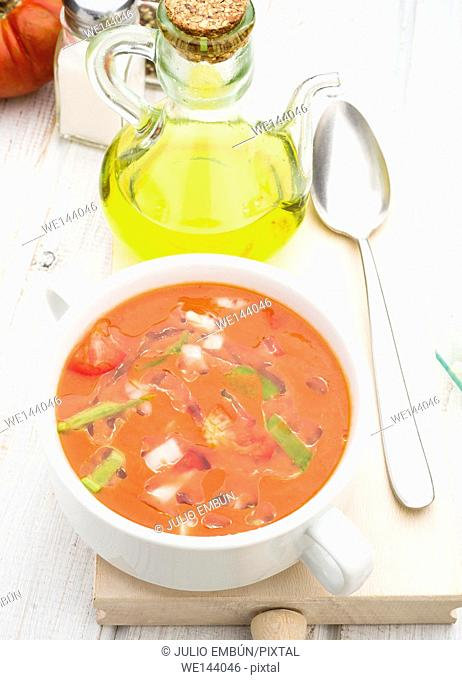 Aerial view of gazpacho soup with oil and spoon in white china bowl