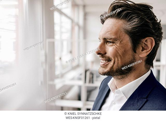Smiling businessman at the window