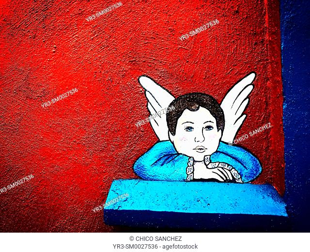 An image of a blue angel decorates a red wall in a street of San Angel, Mexico City, Mexico