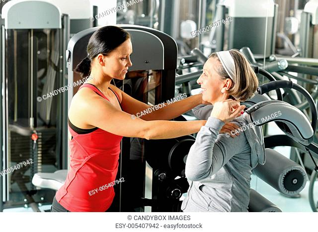 Fitness center senior woman exercise with trainer