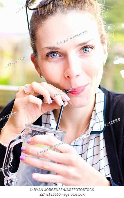 Beautiful young woman in early twenties looking at camera with smile when drinking cold glass of water with slice of lemon at an outdoor restaurant