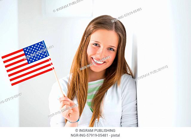 Portrait of a lovely young woman with United State's flag smiling