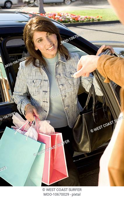 Woman with shopping bags getting out of car portrait