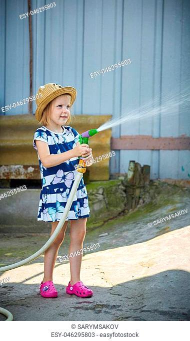 Little girl in hat watering lawn. Summer day