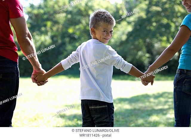 Young boy holding his parents' hands