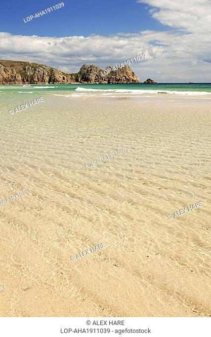 England, Cornwall, Porthcurno. Low tide on the sandy beach at Porthcurno with Logan rock in the distance