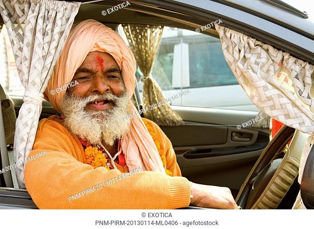 Sadhu sitting in a car and smiling during the first royal bath procession in Kumbh Mela festival, Allahabad, Uttar Pradesh, India