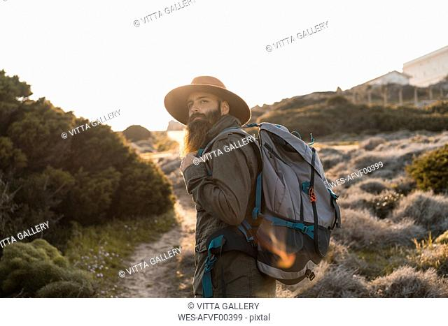 Italy, Sardinia, portrait of bearded hiker with hat and backpack