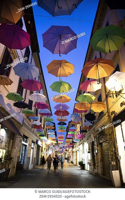A series of umbrellas of different colors hanging along the main road in Pietrasanta Italy