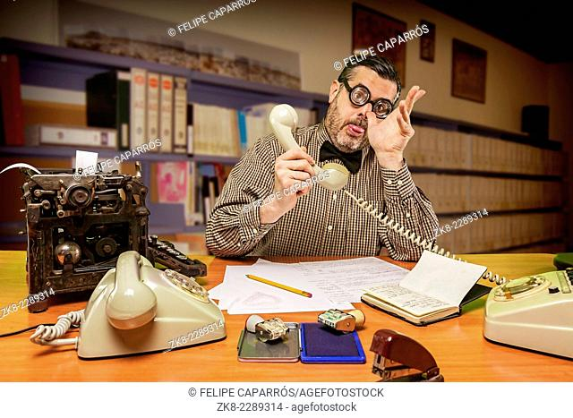 Employee with glasses talking on the phone and making jokes with the hand in the office in the 1960s