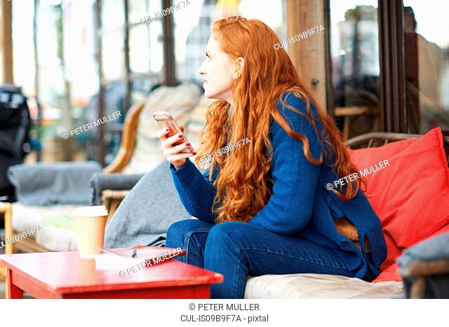 Woman at coffee shop using mobile phone