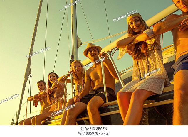 Croatia, Adriatic Sea, Young people on sailboat, sidy by side