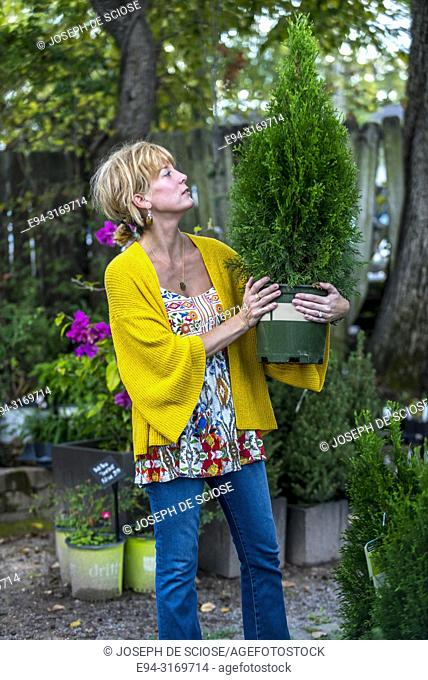 A pretty 42 year old blond woman shopping at a garden store holding a small potted tree