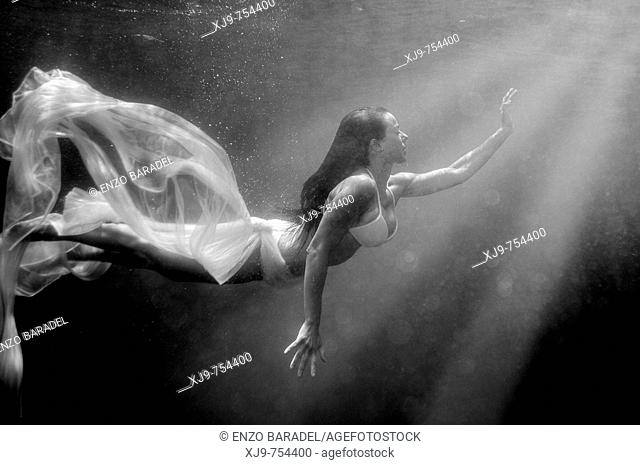 Girl swimming underwater, searching for the light