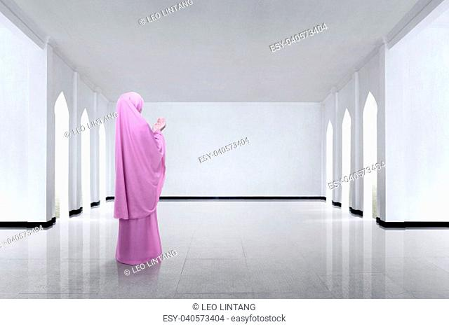Back view of asian muslim woman raising hand and praying on the mosque