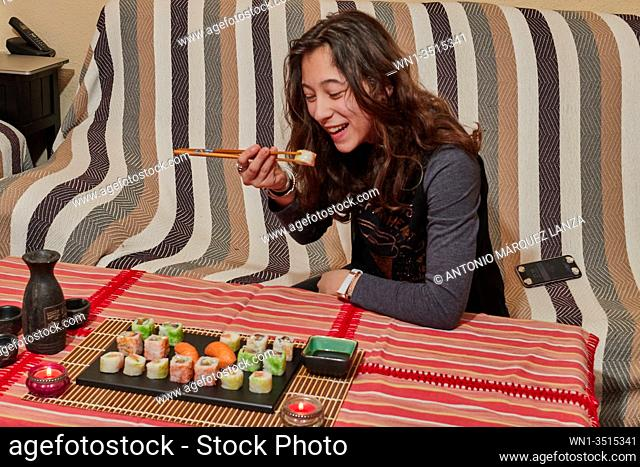Happy lady holds a sushi roll on the chopsticks, looks at delicious Japanese food and smiles, over a table sit on a sofa, wearing cute black clothes