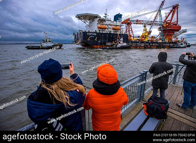 """14 January 2021, Mecklenburg-Western Pomerania, Wismar: Passers-by take pictures of the Russian pipe-laying vessel """"""""Fortuna"""""""" on the pier"""