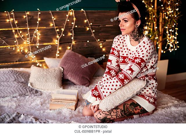 Young woman sitting on bed, wearing christmas jumper, thoughtful expression