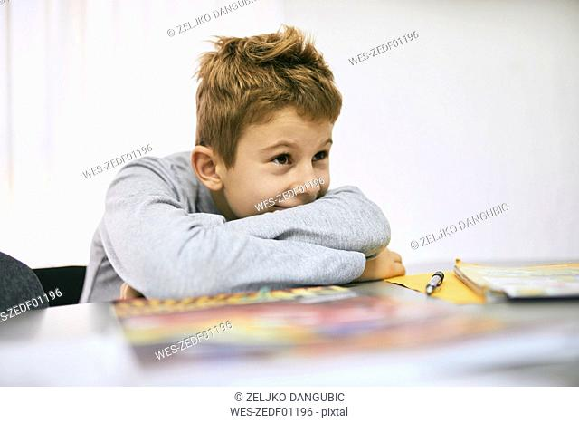 Grinning schoolboy leaning on desk in class