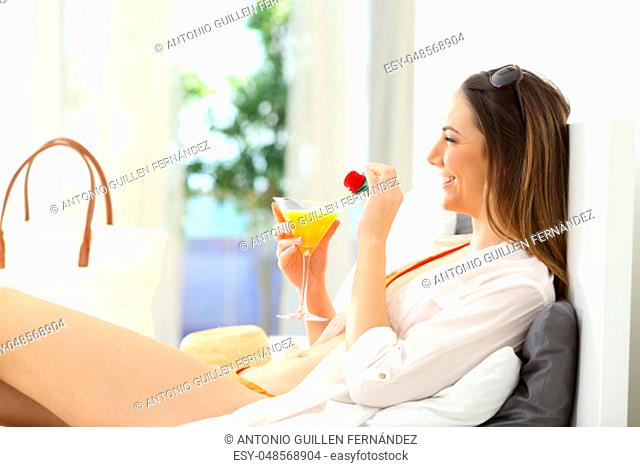 Side view portrait of a happy woman enjoying summer vacation in an hotel room