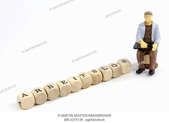 Miniature figure of an unemployed worker, letter cubes forming the word arbeitslos, German for unemployed