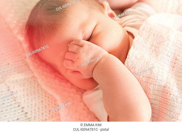 Baby covering eye in sleep