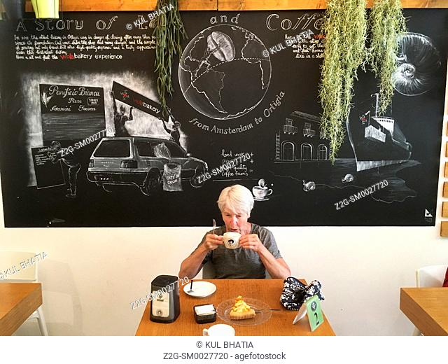 A woman having a cappuccino in a cafe, Siracusa, Sicily. The board in the background outlines the history of coffee and this cafe