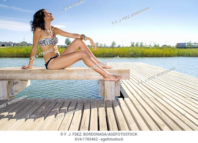 Young girl relaxed with bikini at lake in summertime