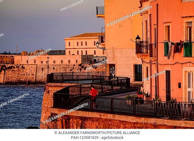 Syracuse, Ortegia, Sicily, Italy A runner in the old town at dawn. | usage worldwide. - Syracuse/Sicily/Italy