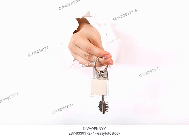 hand holds the keyring through a hole in a sheet of paper