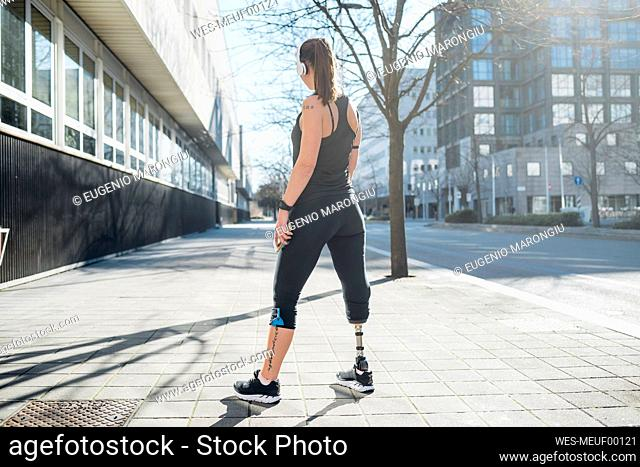 Sporty young woman with leg prosthesis standing in the city