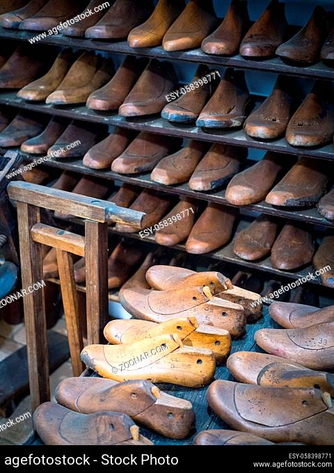 Shoemakers model for shoes in his workshop
