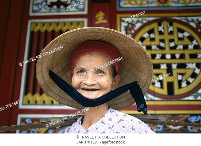 Street Scene / Elderly Woman / Traditional Architecture in Background, Hoi An, Vietnam