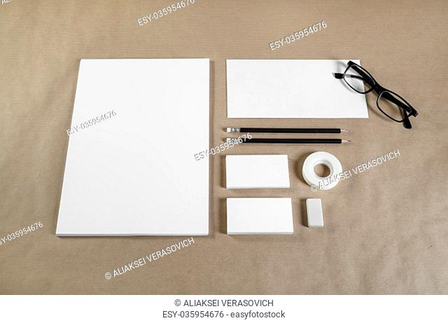 Photo of blank stationery set on craft paper background. Responsive design template. Top view