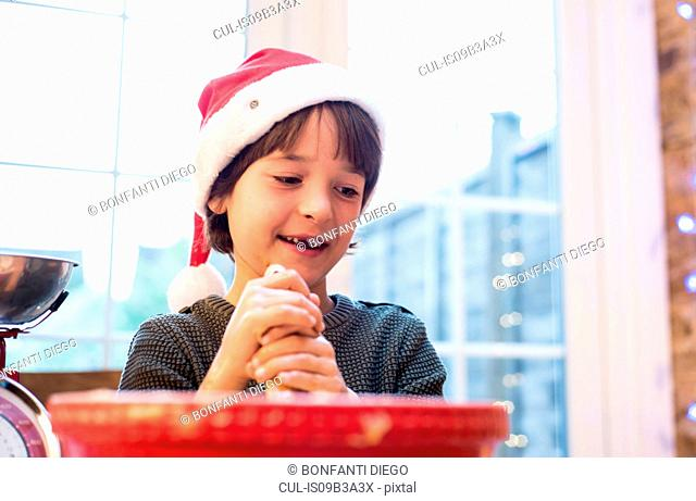 Portrait of boy holding rolling pin, smiling