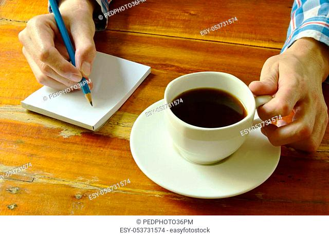 hand writing on book while drinking black coffee
