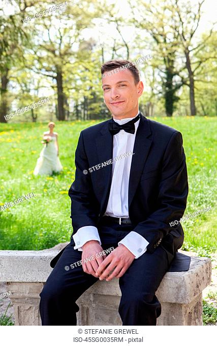 Smiling groom sitting on wall